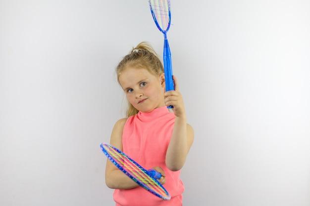 Un niño sostiene dos raquetas de tenis azules. pose de deportes. entretenimiento