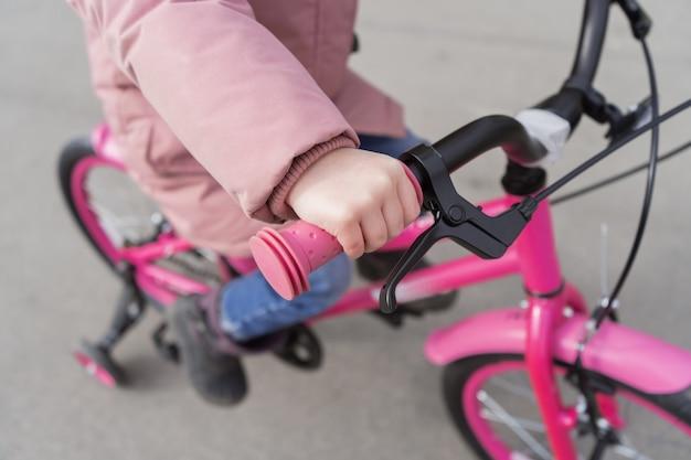 El niño sostiene la rueda de una bicicleta. una niña en una chaqueta rosa está montando su bicicleta.