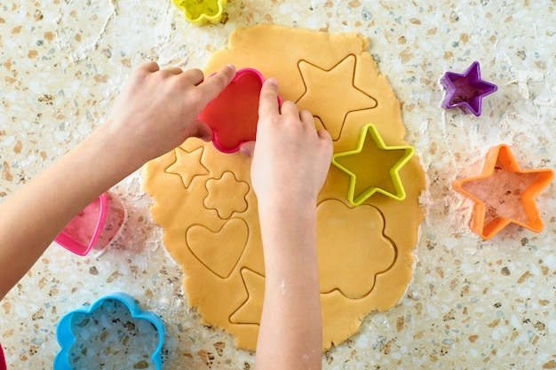 Un niño con su madre hace galletas, extiende la masa y usa moldes para hacer galletas.