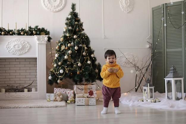 Niño con un suéter amarillo sostiene una estrella dorada de navidad en sus manos y sonríe cerca del árbol de navidad y una chimenea.