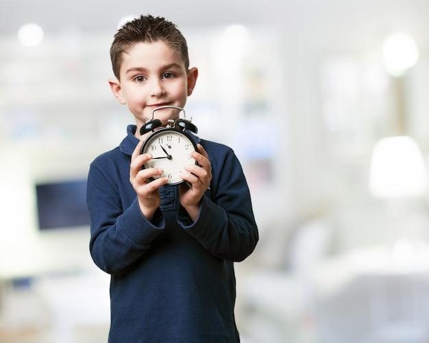 Niño sujetando un reloj despertador