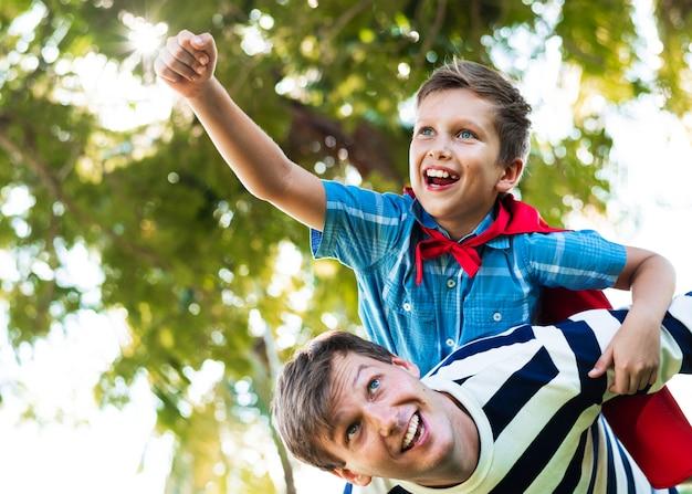 Niño superhéroe volando en la espalda de su papá