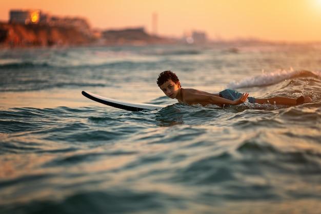 Niño surfeando en playa tropical