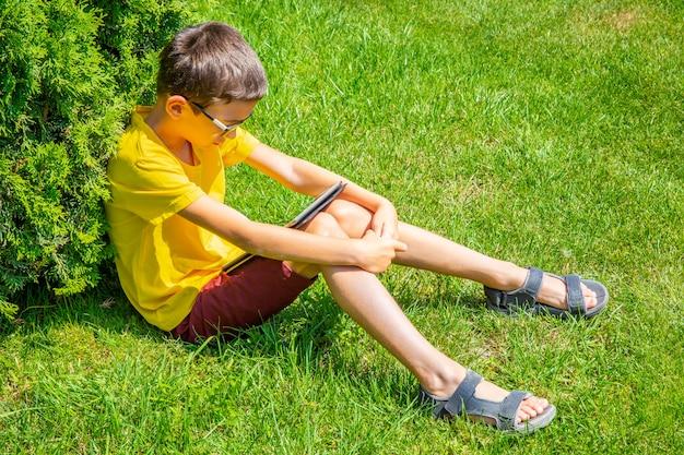 Niño con tablet pc en césped de hierba verde