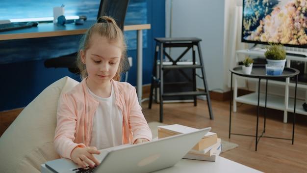 Niño con teclado en la computadora portátil para tareas y cursos en línea