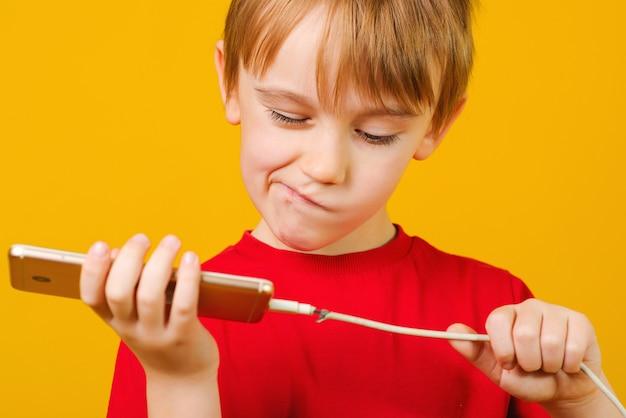 Niño con un teléfono móvil con un cable de carga defectuoso.