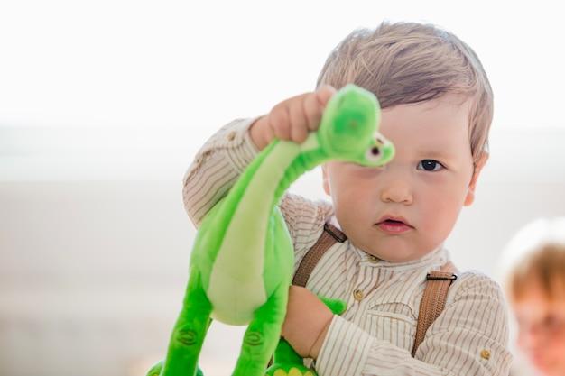 Niño, tenencia, dinosaurio, juguete, mirar, cámara