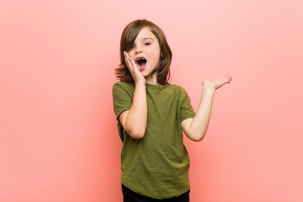 Niño tiene espacio de copia en una palma, mantenga la mano sobre la mejilla. sorprendido y encantado.