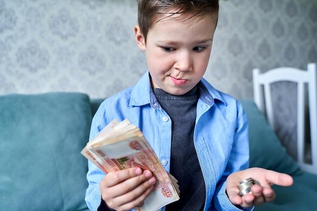 El niño tiene mucho dinero en una mano y monedas pequeñas en la otra y tiene dudas.