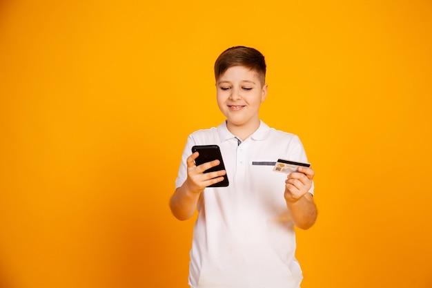 El niño tiene una tarjeta de crédito y el teléfono inteligente hace compras. feliz joven utiliza un teléfono inteligente y una tarjeta bancaria para comprar en línea.