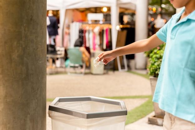 Niño tirando papel de seda blanco en un contenedor de basura.