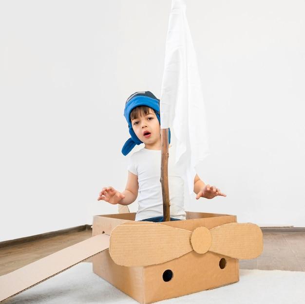 Niño de tiro completo en bote de cartón