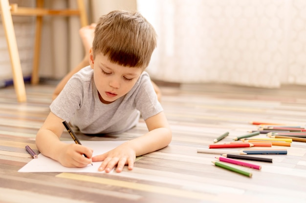 Niño de tiro completo en el dibujo del piso
