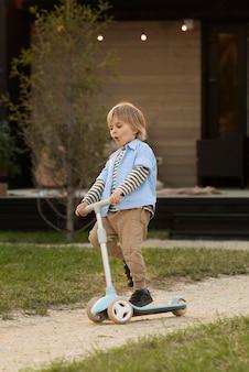 Niño de tiro completo jugando con scooter