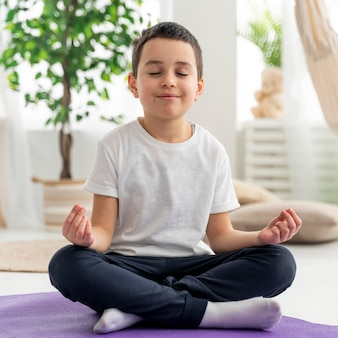 Niño de tiro completo meditando sobre estera