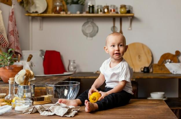Niño de tiro completo sentado en la mesa