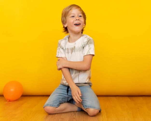 Niño de tiro completo sentado en el piso