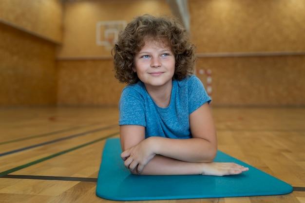 Niño de tiro completo tendido sobre una estera de yoga