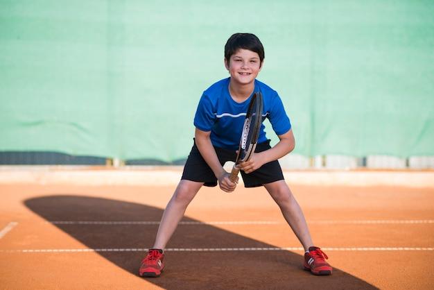Niño tiro largo jugando tenis