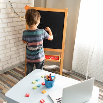 Niño de tiro largo que asiste a cursos de la escuela virtual