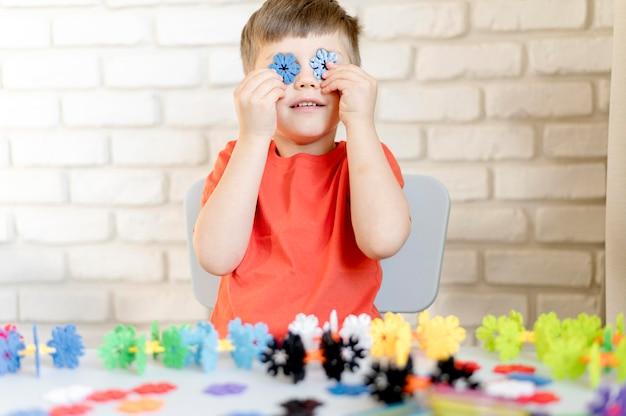Niño de tiro medio con copos de nieve de plástico