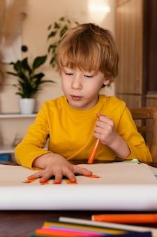 Niño de tiro medio dibujando su mano