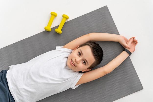 Niño de tiro medio en estera de yoga