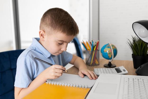 Niño de tiro medio estudiando en casa