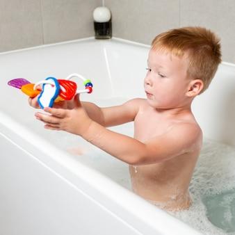Niño de tiro medio con juguete en la bañera