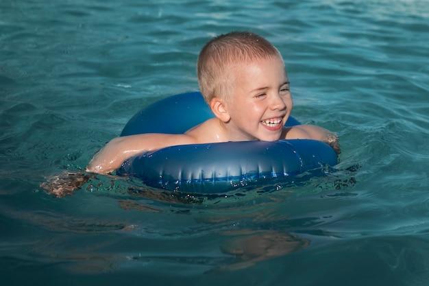 Niño de tiro medio nadando con aro salvavidas