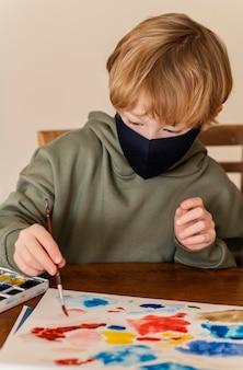 Niño de tiro medio con pintura de máscara