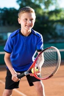 Niño de tiro medio preparándose para servir la pelota.