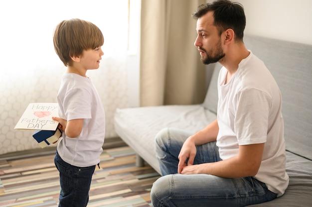 Niño de tiro medio con sorpresa para padre