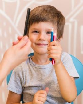 Niño de tiro medio sosteniendo crayones