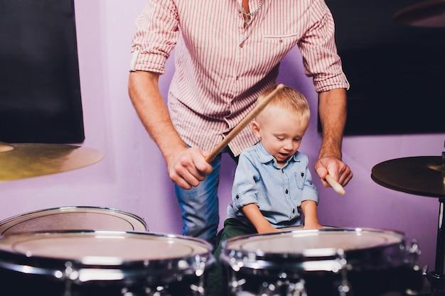 Niño toca la batería en el estudio de grabación.