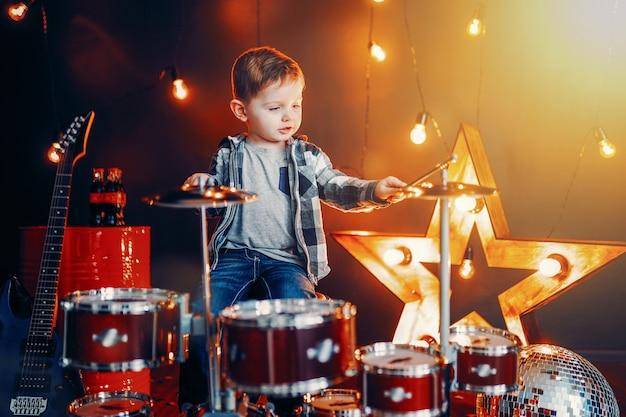Niño tocando la batería en el escenario