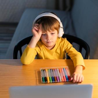 Niño tomando cursos virtuales y con marcadores de colores.