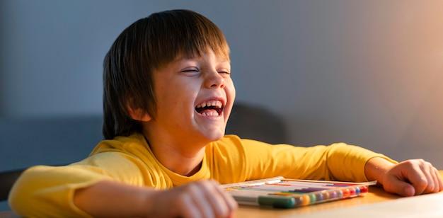 Niño tomando cursos virtuales y riendo.