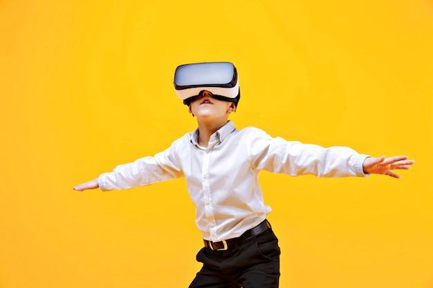 Niño en traje formal con gafas de realidad virtual poniendo las manos en emoción aislado