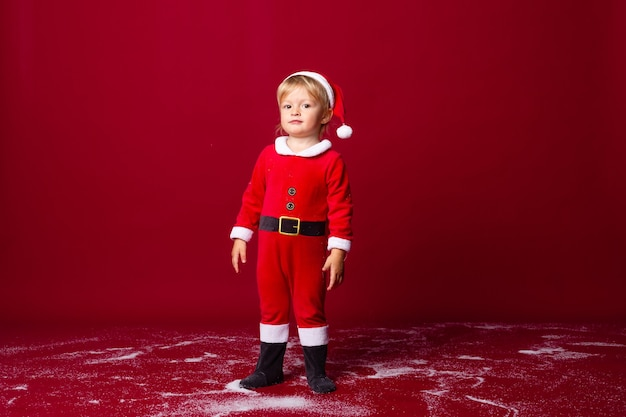 Niño en traje de santa sonríe contra el fondo rojo, espacio para texto