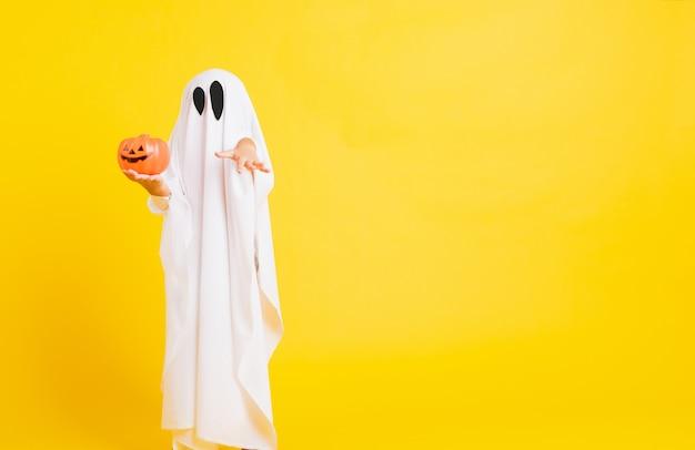 Niño con traje vestido de blanco fantasma de halloween tenebroso fantasma de calabaza naranja en la mano