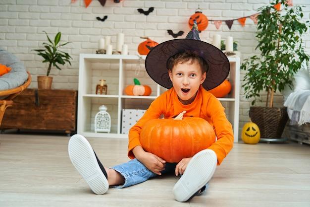 Niño travieso en traje y sombrero para halloween con calabazas