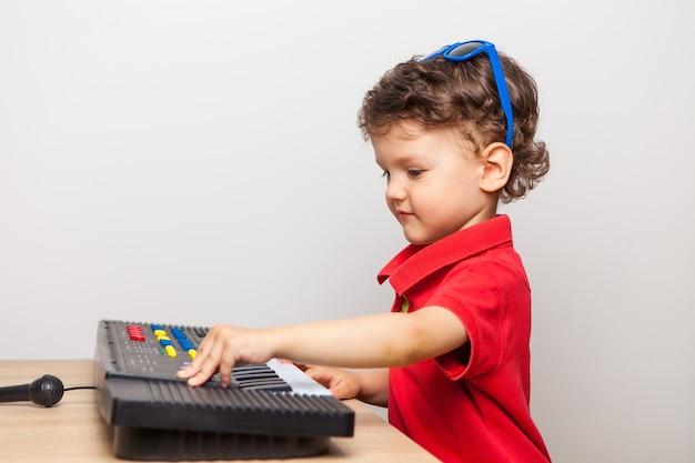 Un niño de tres años aprende a tocar un sintetizador de juguete, ajusta botones y organiza un concierto en casa durante la cuarentena.