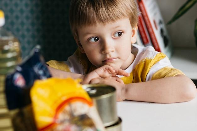 Niño triste con comida donada. concepto de entrega de comida.