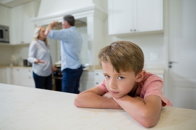 Niño triste escuchando a sus padres discutiendo