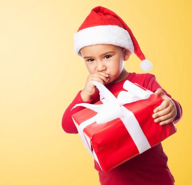 Niño triste sujetando un regalo con fondo naranja