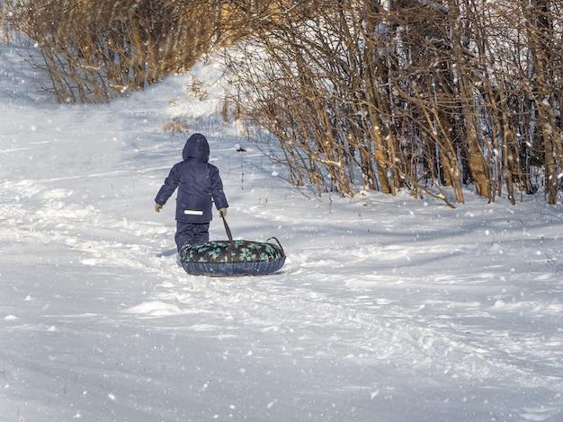 Niño con tubos sube a la montaña. niño divirtiéndose en el tubo de nieve