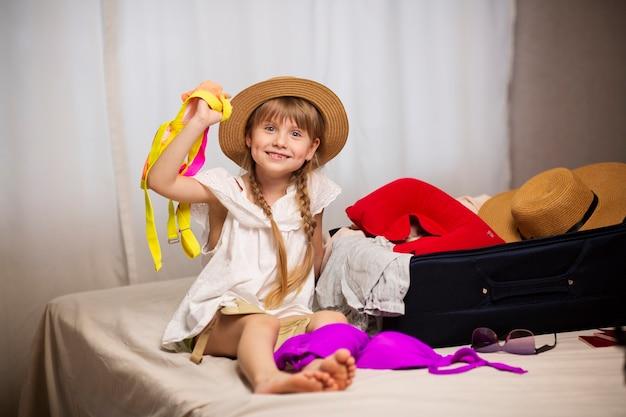 Niño turista sentado en la cama junto a una maleta con ganas de volar en un avión soñando con viajar prepara su bolsa de equipaje de viaje para su aventura