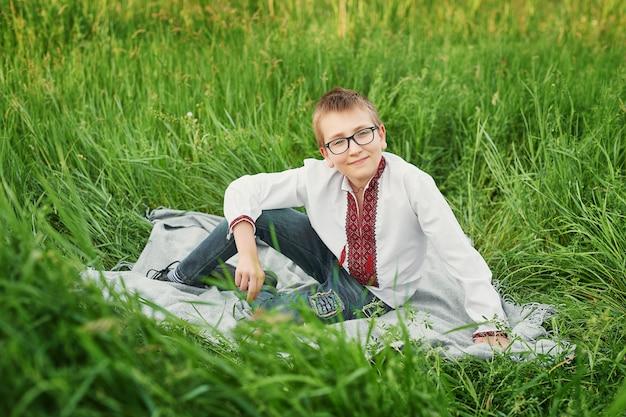 Niño ucraniano niño en bordado en el campo
