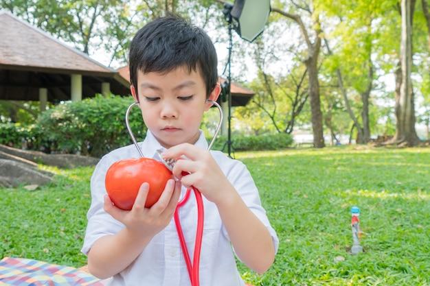 Niño usa estetoscopios y juega con el símbolo de tomate de fruta